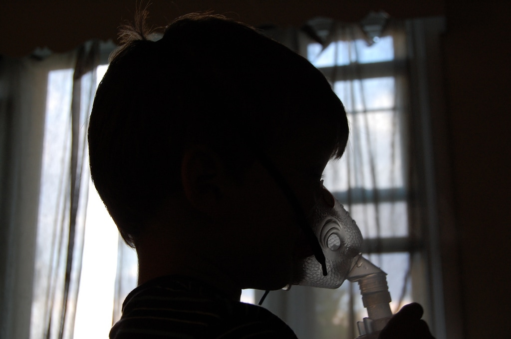 Silhouette of young boy with asthma inhaler